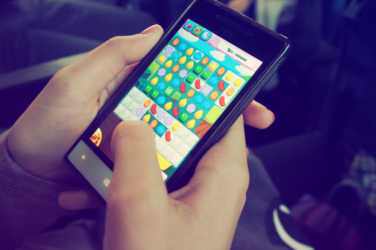 Hands playing candy crush on their mobile phone