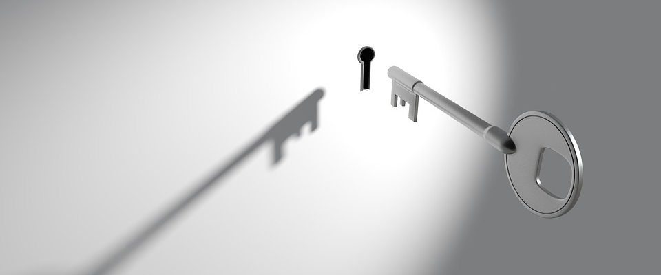 Silver key in front of keyhole in white wall