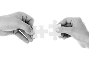 Two hands connecting jigsaw pieces