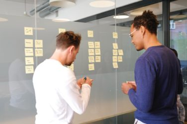 Two people looking at a board of sticky notes
