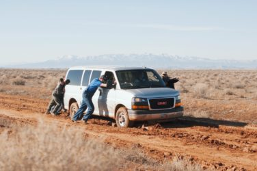 People pushing broken down car in desert